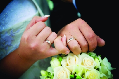 10159825 - hands with rings and wedding bouquet