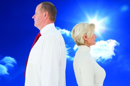 Older couple standing not facing each other against bright blue sky with clouds